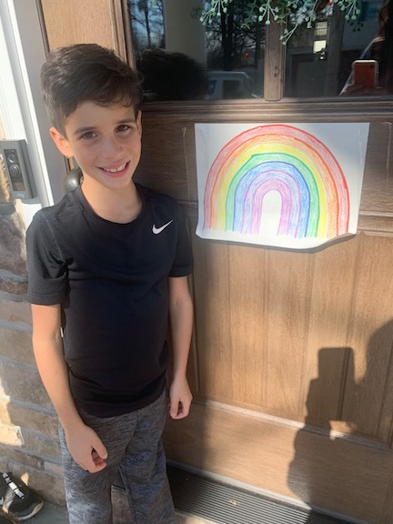 a boy standing next to his rainboy on a door