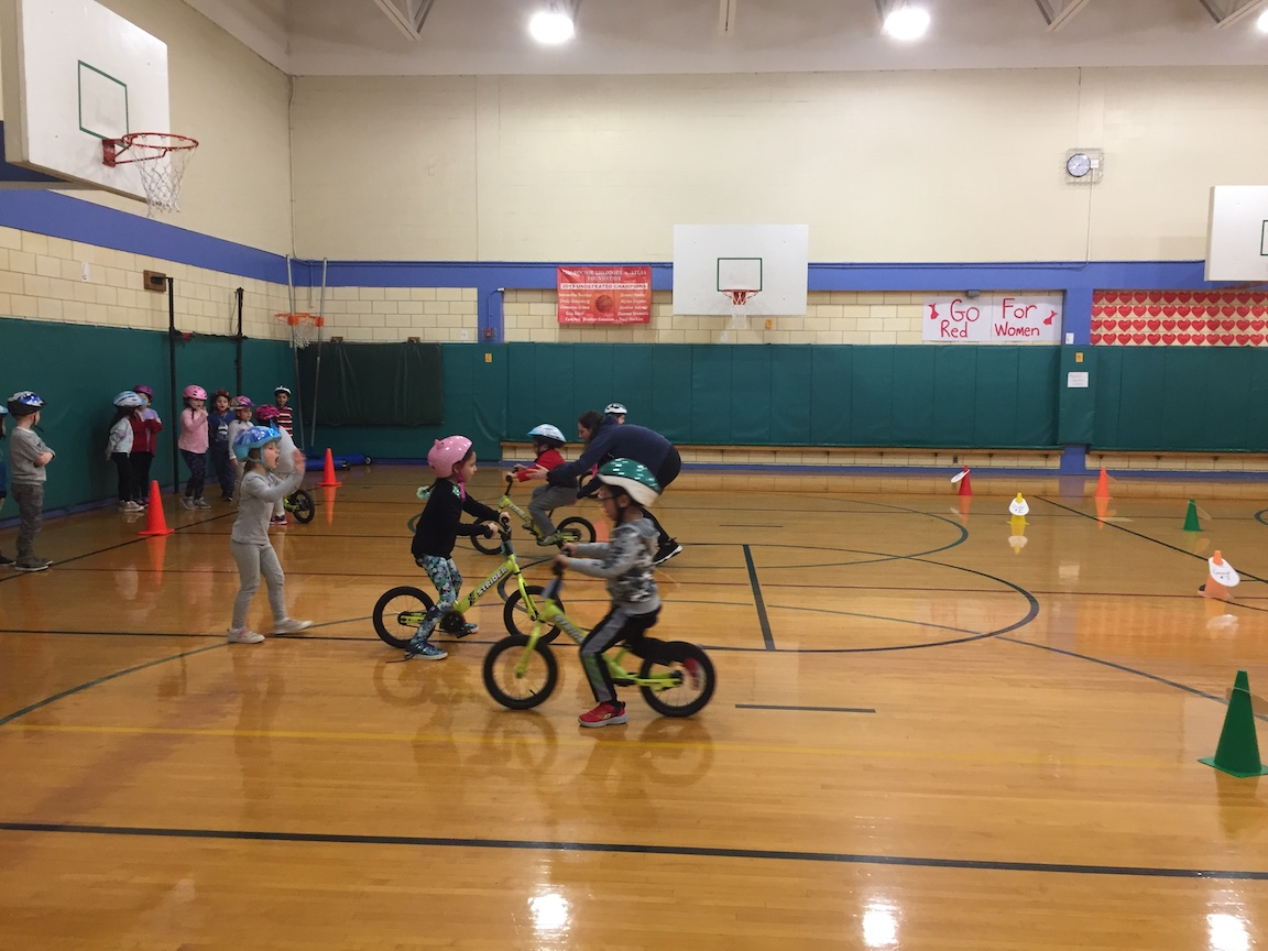 a group of children practicing on their bikes