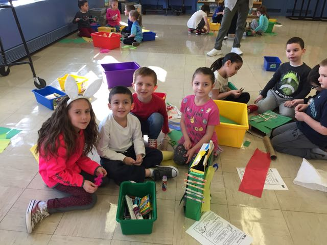 many groups of children working on their projects on the floor