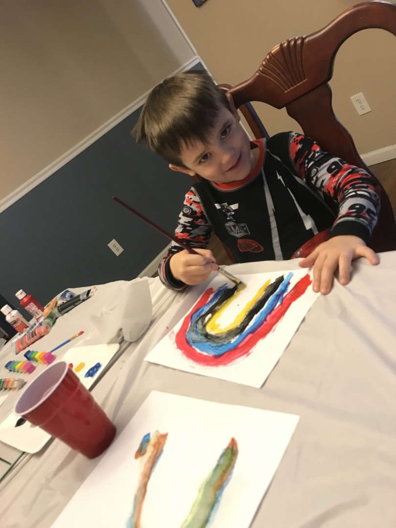 a young boy drawing a rainbow