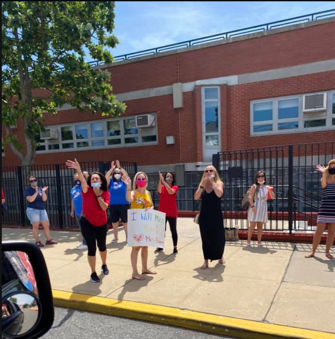 The teachers with signs waving to the 5th graders