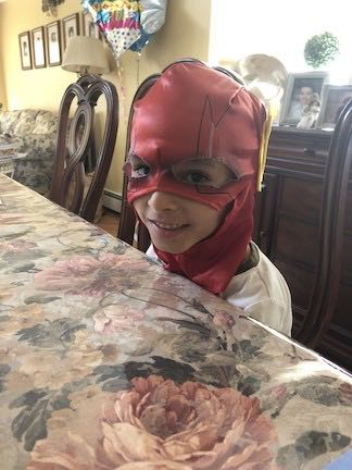 This little boy is wearing a red head mask