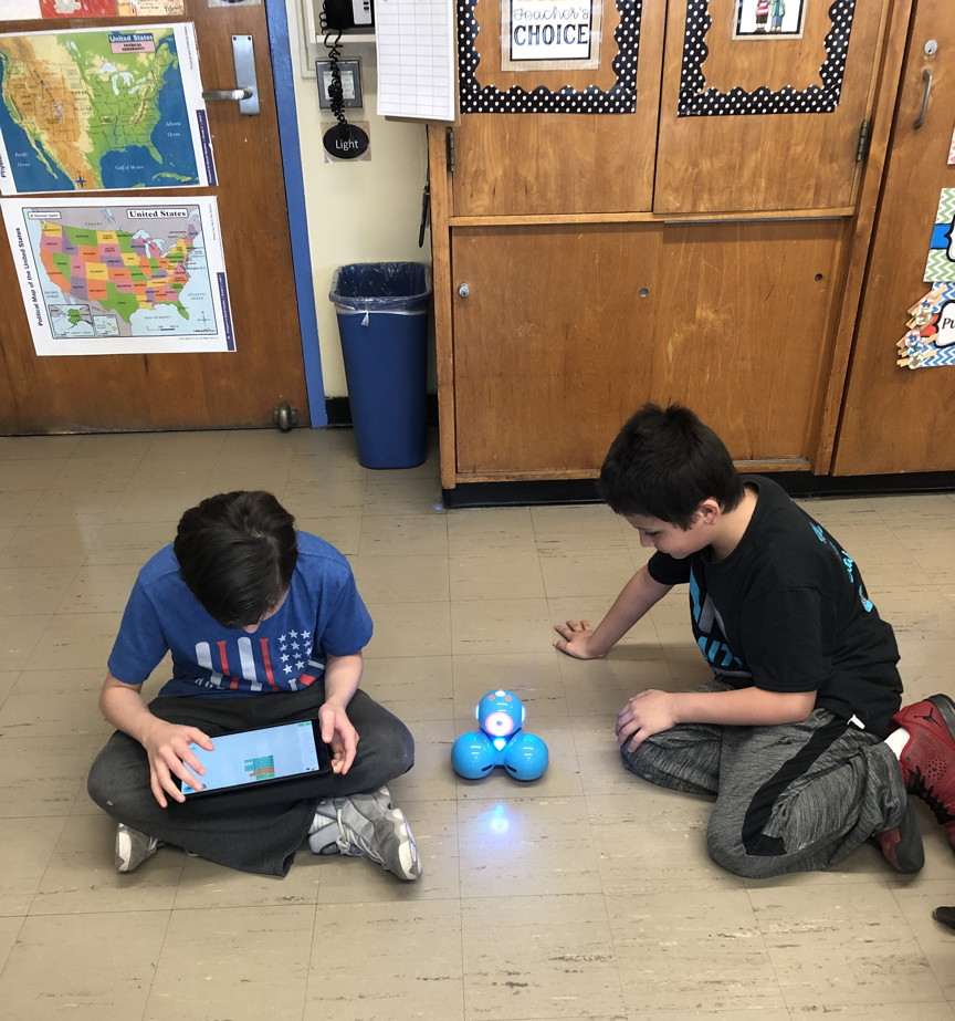 two boys figuring out the robot's next move
