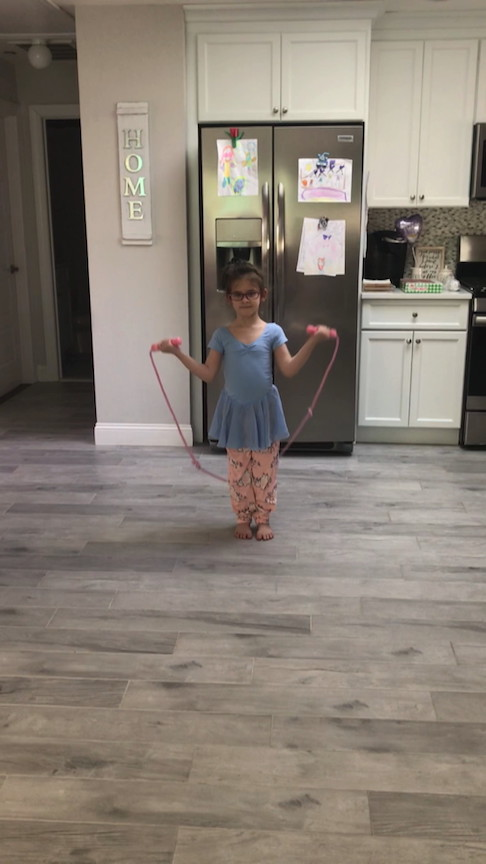 a little girl trying to jump rope in her kitchen
