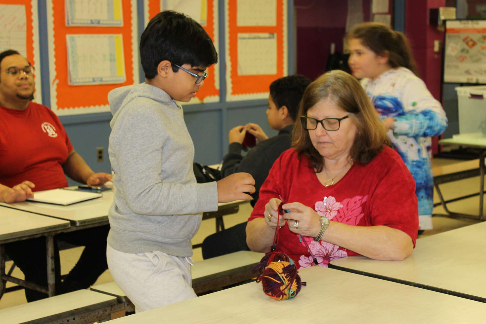 Mrs. Fishman being coached as she tries knitting