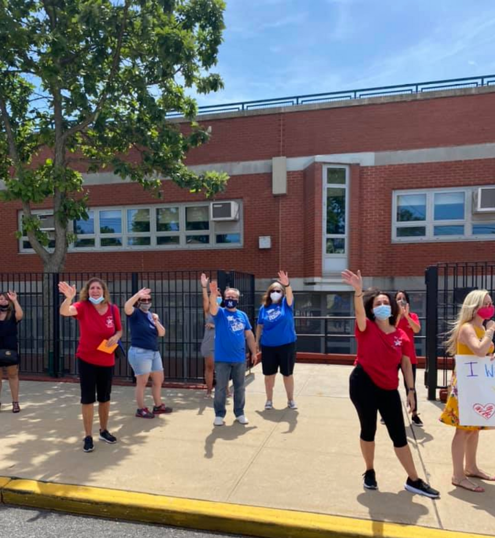 The principal, assistant principal and some of the faculty waving to the 5th graders