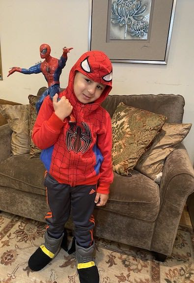 a boy dressed as Spiderman holding a Spiderman doll