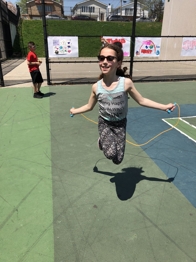 a girl in sunglasses jumping rope