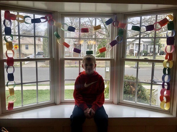 a child sitting in a bay window decorated with a paper chain of different colored links
