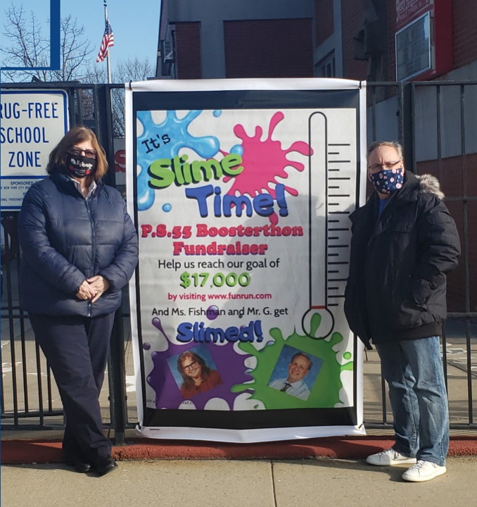 Principal and Assistant principal in front of a poster to join FUNRUN.com fundraisere for the school.