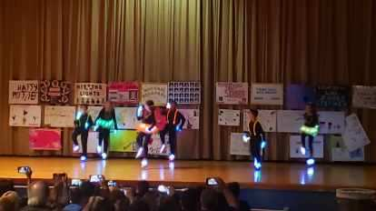 a group of students performing a dance dressed in lights