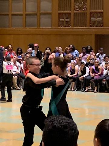boy wearing glasses and his partner performing