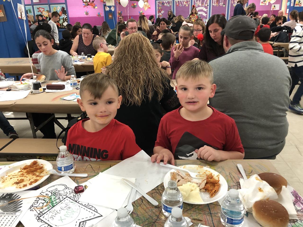 two boys eating dinner