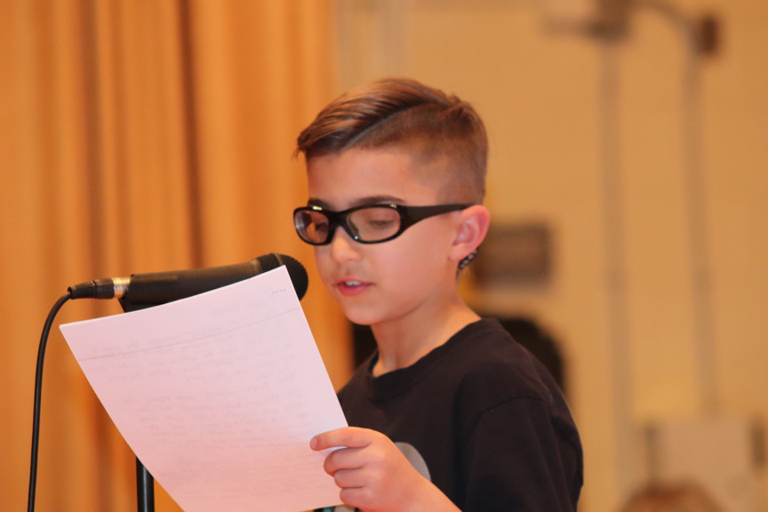 a boy reading in front of a mic