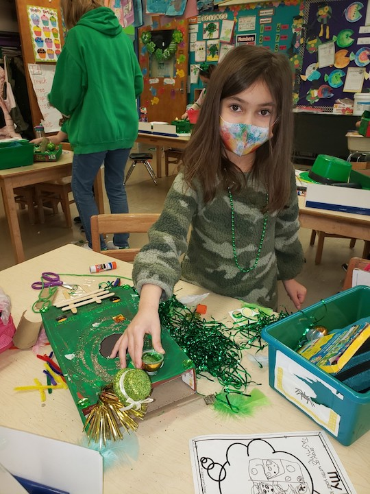 A girl decorating a box in green decorations