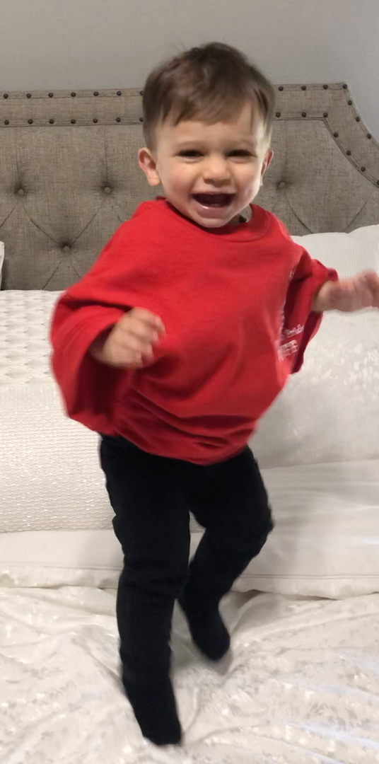 This adorable child is jumping on the bed.