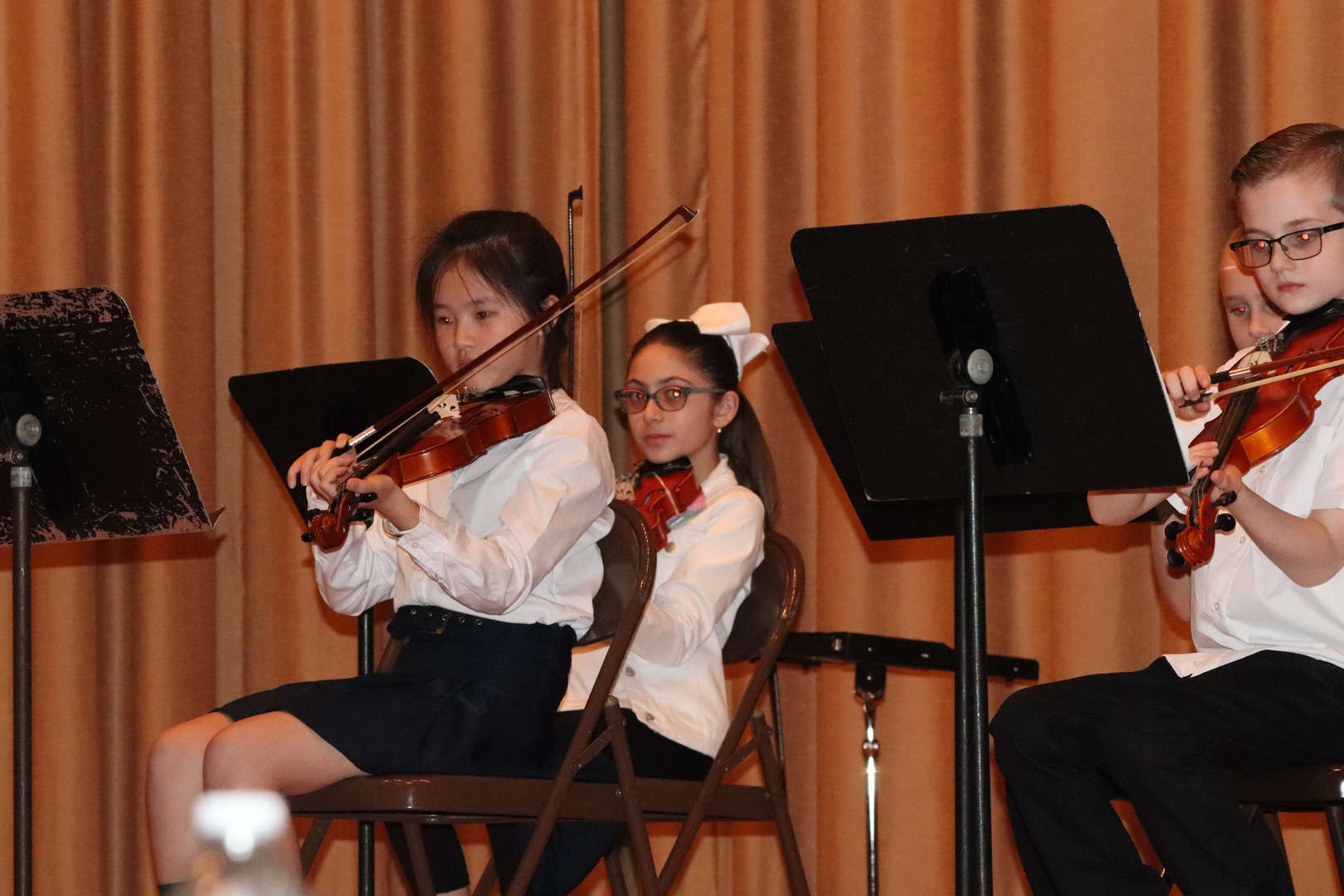 two girl violinists reading the music