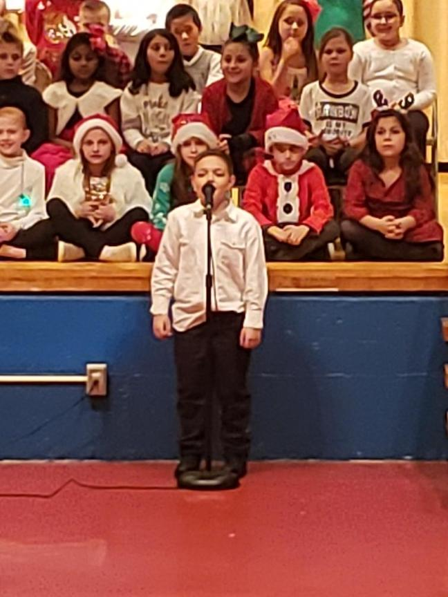 a boy student singing a solo