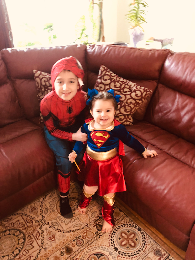 Here is a boy and his little sister dressed like superheroes