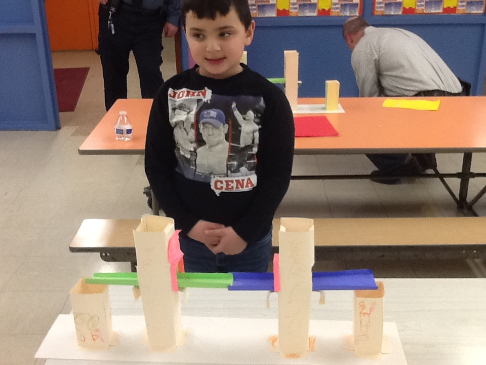 a student standing by the bridge he built