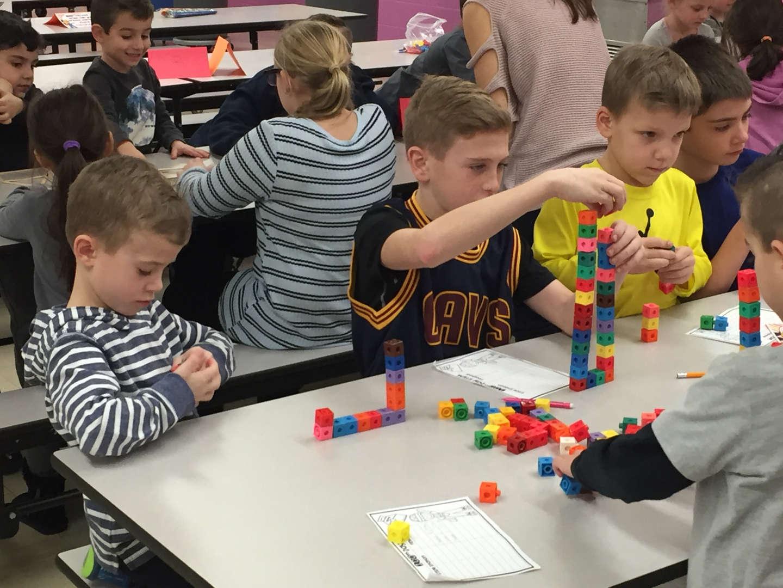 Children doing a math activity with cubes