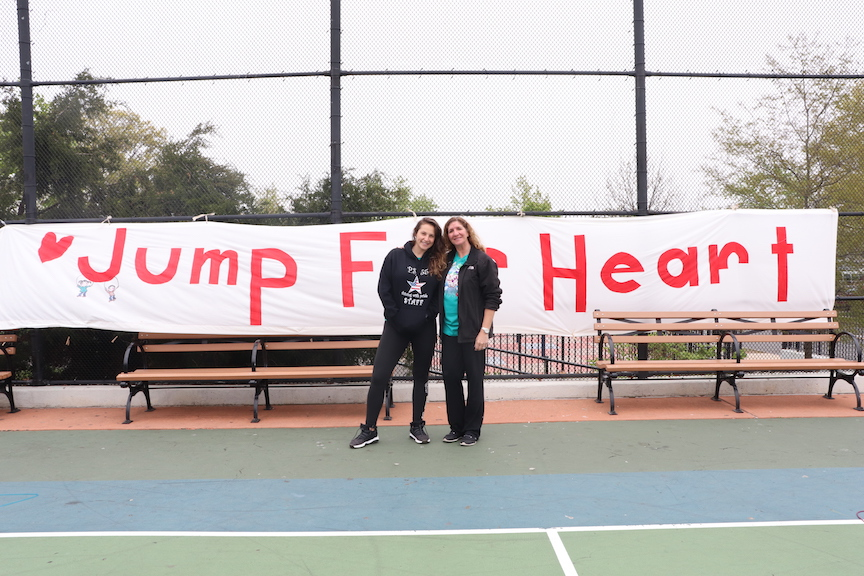 The gym teachers in front of the Jump for Heart banner