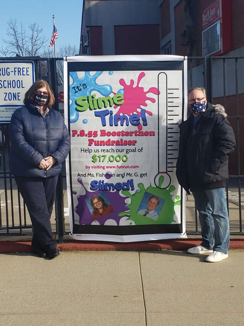 Principal and Assistant Principal in front of a poster. It says they will be slimed if we reach our fundraising goal.