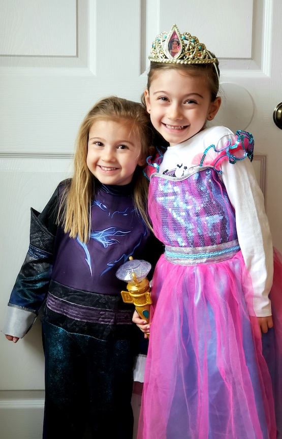 two smiling girls in their costumes