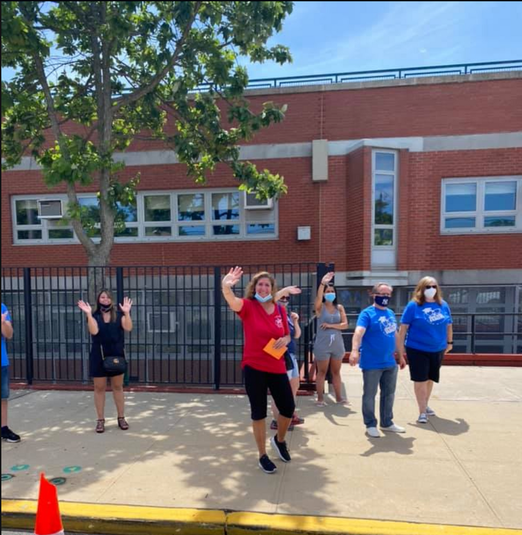 a group of teachers waving to the 5th graders passing by