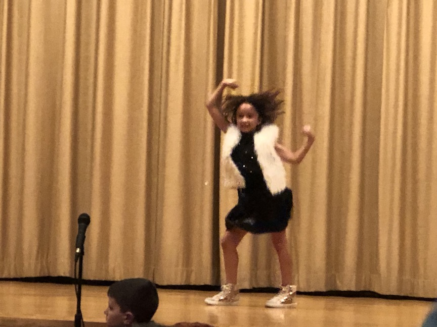 a girl in a white vest dancing