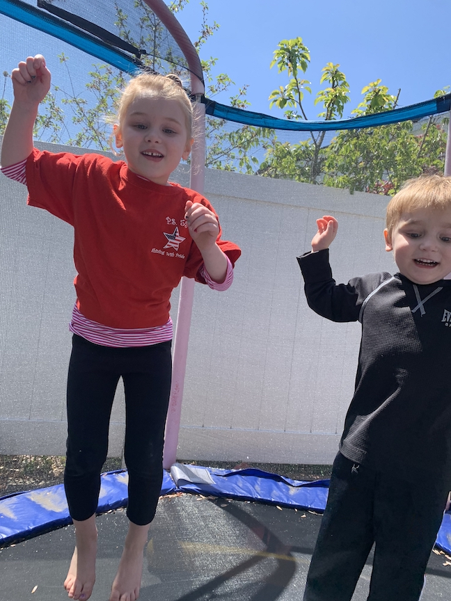 Here's a boy and girl jumping on their trampoline