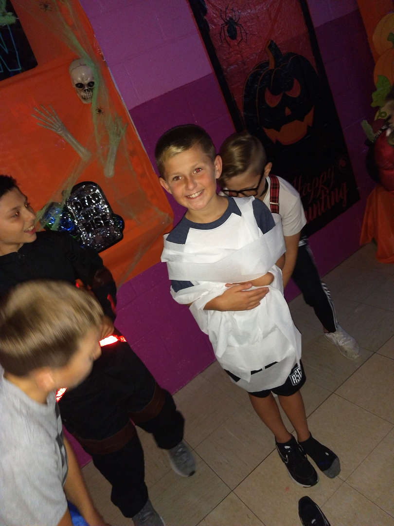a boy is being wrapped in toilet paper to look like a mummy