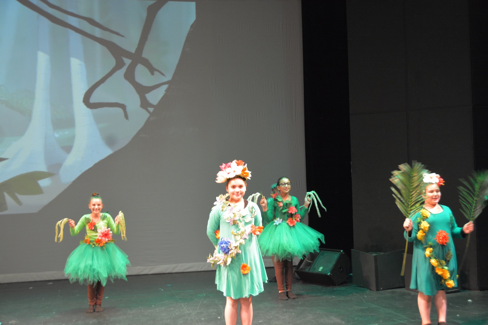 4 dancing girls dress in green costumes with flowers