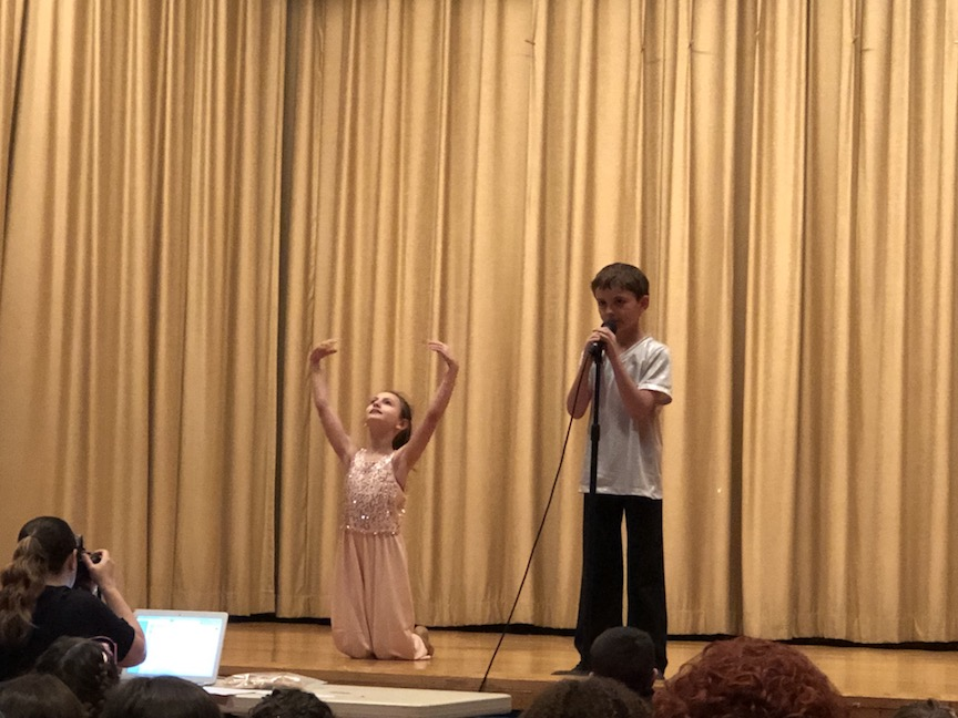 a boy singing while a girl dances