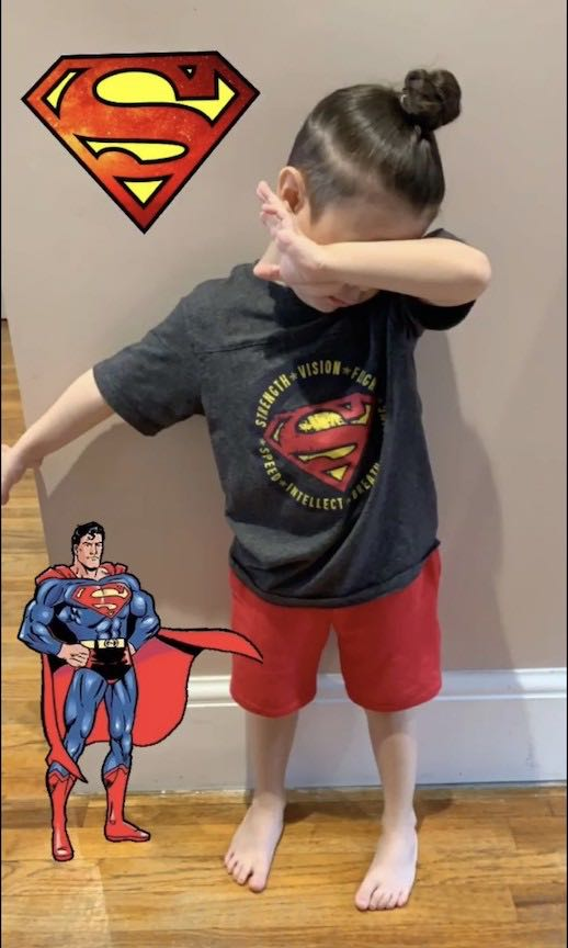 This girl is dabbing while wearing a Superman shirt
