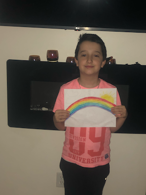 a boy proudly holding up his rainbow