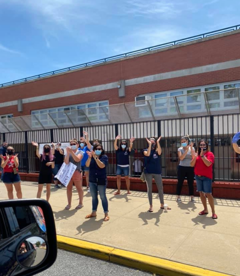 A large group of the staff waving to the 5th graders