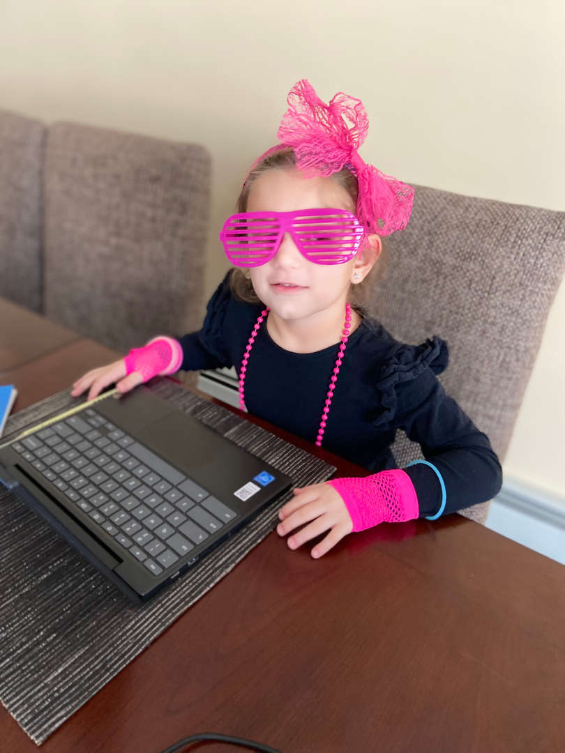 a girl in pink and black sitting with a laptop wearing pink glasses