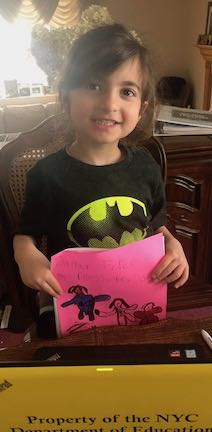 a girl in a batman tee holding her story