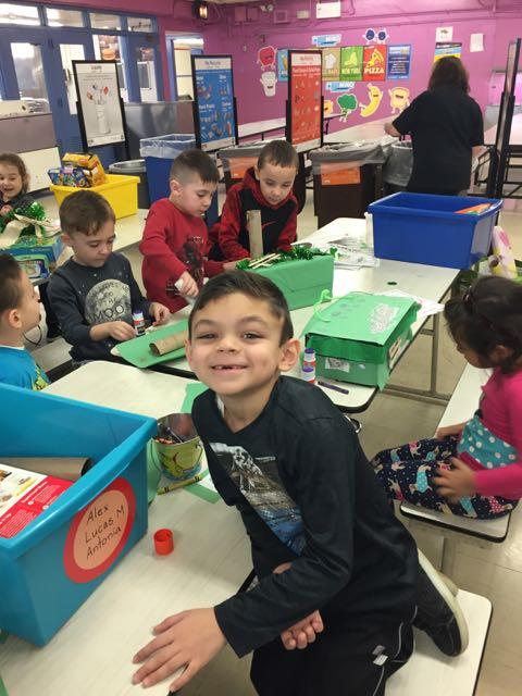 a boy smiling at the camera as his group keeps working