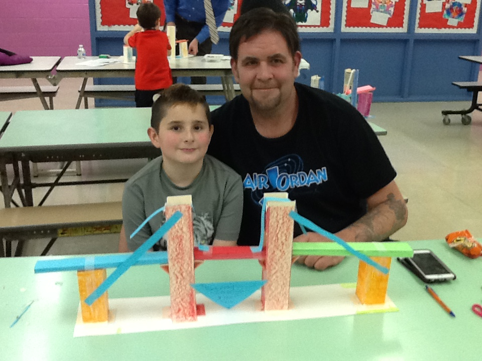 Student showing his bridge to his father