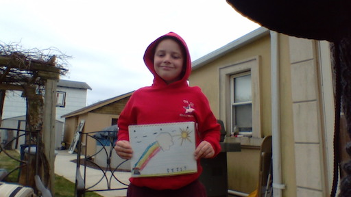 a child outside in a red hoodie with their rainbow