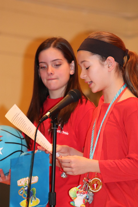two girls reading into a microphone