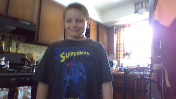 a boy dressed in a Superman shirt