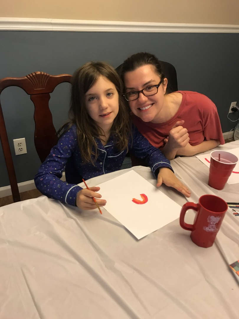 mother next to her daughter as she draws a rainbow