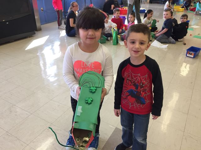 a boy and girl showing their project