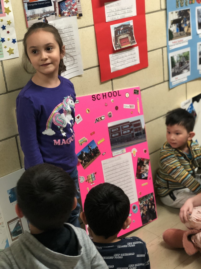 a girl showing her project to students