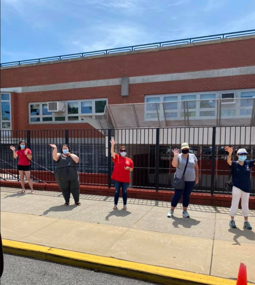 five teachers waving to the 5th graders