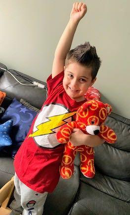 a little boy wearing a superhero shirt holding his teddy