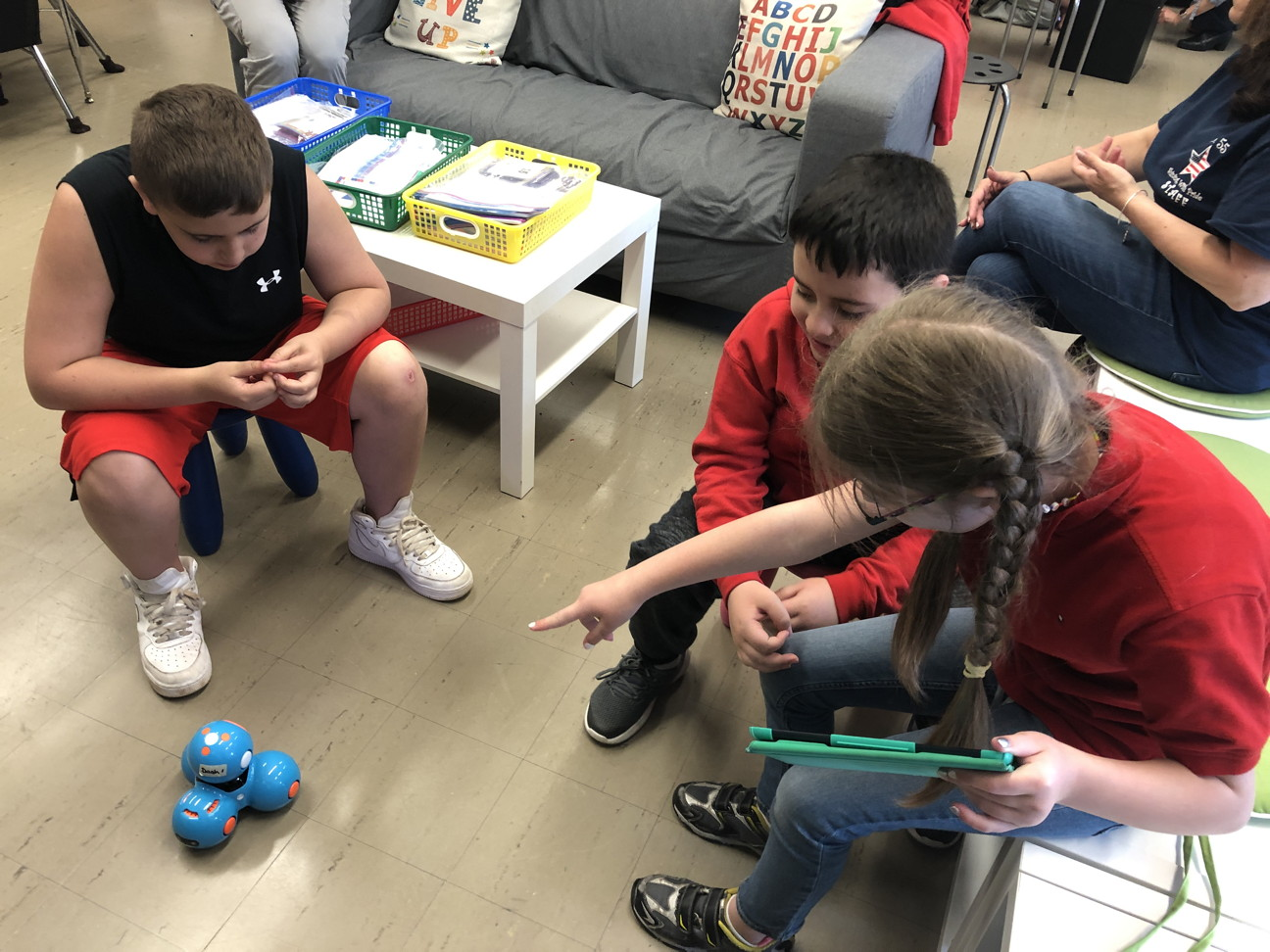 Three children helping the robot move